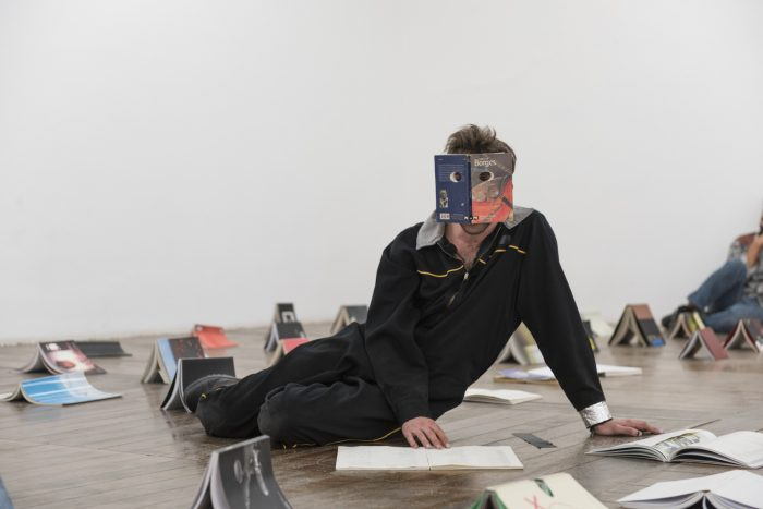 Victor del Moral,Fake- book(Lecto-sculpture No. 9), 2017. Installation/action, Books, body, words; variable dimensions. Vermehlo Gallery at Festival Verbo, São Paulo, Brazil. Photo by Edouard Fraiponto. Image courtesy of Galeria Vermehlo